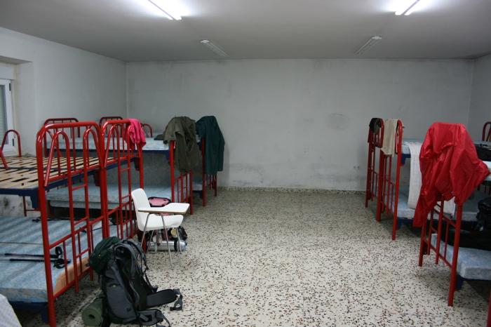 Rote Gitterbetten in einem kargen Übernachtungsraum