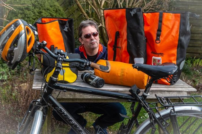 Mensch hockt hinter leeren Fahrradtaschen und packt.